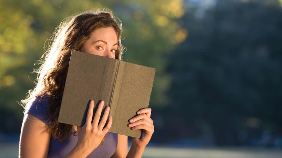 'Woman posing with book outdoors'