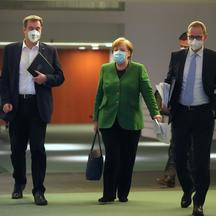 Germany's Merkel walks with Bavarian State Premier Soeder and Berlin Mayor Mueller after discussing COVID-19 lockdown extension with state premiers