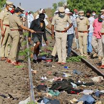 Police officers examine the railway track after a train ran over migrant workers sleeping on the track in Aurangabad district