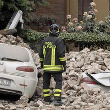 'A firefighter stands next to damaged cars after an earthquake in Finale Emilia May 20, 2012. A strong earthquake rocked a large swathe of northern Italy early on Sunday, killing at least three people
