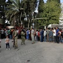 FILE PHOTO: People stand in a queue to get bread in the border town of Tal Abyad