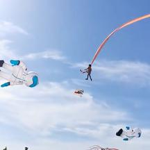 A child is pulled up in the air by a kite at an International Kite Flying Festival, in Hsinchu