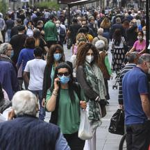 A crowd of people wearing protective masks walk in Naples center