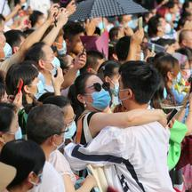 "Woman embraces a student during annual national college entrance exam, or ""gaokao"", in Wuhan"