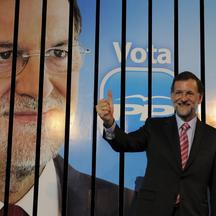 'Leader of the Spanish opposition party Partido Popular (PP) and candidate for general elections, Mariano Rajoy gives the thumb up in front of an election poster during a meeting marking the start of