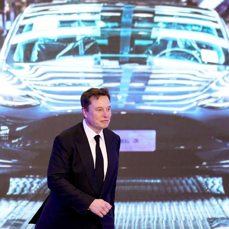 FILE PHOTO: Tesla Inc CEO Elon Musk walks next to a screen showing an image of Tesla Model 3 car during an opening ceremony for Tesla China-made Model Y program in Shanghai