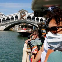 Tourists wear face masks as they pass the Rialto Bridge on a vaporetto (water taxi), amid the coronavirus disease (COVID-19) outbreak, in Venice