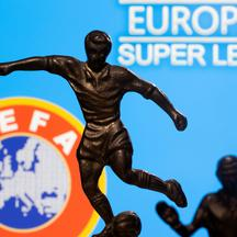 "FILE PHOTO: Metal figures of football players are seen in front of the words ""European Super League"" and the UEFA logo in this illustration"