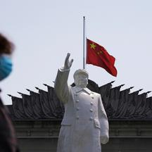 FILE PHOTO: The Chinese national flag flies at half-mast behind a statue of late Chinese chairman Mao Zedong in Wuhan