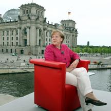 'German Chancellor Angela Merkel has taken her seat to give her traditional summer interview to German public tv chain ARD on July 17, 2011 in Berlin. In background can be seen the Reichstag housing t