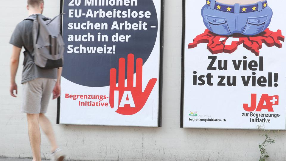 Man walks past posters against the anti-immigration initiative in Zurich