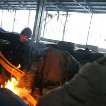 Migrants warm up in an abandoned factory near Velika Kladusa