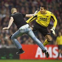 'Goalkeeper Esteban of AZ Alkmaar (R) kicks a man who attacked him from behind during their football cup match against Ajax at the Arena stadium in Amsterdam, on December 21, 2011. AZ Alkmaar cancelle