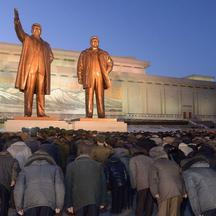North Koreans bow to bronze statues of North Korea's late founder Kim Il Sung (L) and late leader Kim Jong Il at Mansudae in Pyongyang, in this picture taken on December 16, 2014 and provided by Kyodo December 17, 2014, to mark the third death anniversary
