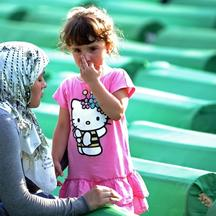 \'A Bosnian Muslim woman comforts a child among the 613 coffins laid out in preparation for mass burrial ceremony at the Srebrenica Memorial Cemetary in Potocari on July 10, 2011. Tens of thousands of
