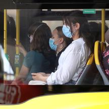 People wear face masks as they use a public transport bus in Berlin