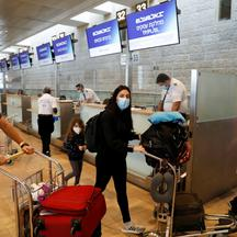 Passengers wearing masks push trolleys at the departures terminal at Ben Gurion International Airport, in Lod, near Tel Aviv, Israel