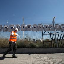 "A man walks past shirts hanging from a fence with sings reading ""Future for Nissan, now"" at Nissan factory at Zona Franca during the coronavirus disease (COVID-19) outbreak in Barcelona"