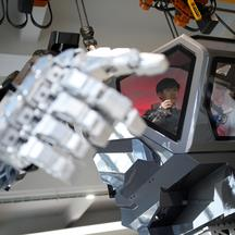 An employee controls the arms of a manned biped walking robot