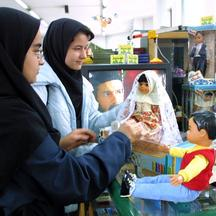 'Iranian girls check out locally-made dolls, Sara (L) and Dara (R), at a toy shop in Tehran 17 March 2002. Iran released its twin national dolls on the market recently with Sara dressed in traditional