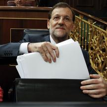 'Spain's Prime Minister Mariano Rajoy takes documents from his briefcase in parliament in Madrid, July 11, 2012.  Rajoy said on Wednesday he would raise the value-added tax by 3 percentage points to