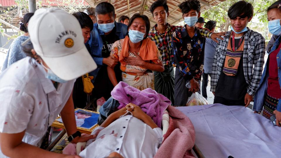 Family members cry near dead body of a teenage boy Tun Tun Aung who was shot dead by security forces in front of his home in Mandalay