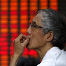 An investor looks at an electronic board showing stock information at a brokerage house in Shanghai, China, July 10, 2015. Chinese stocks rose strongly for a second day on Friday, buoyed by a barrage of government support measures, but worries persist abo