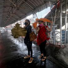 Women take shelter at a pedestrian overpass during heavy rains caused by Cyclone Tauktae in Mumbai