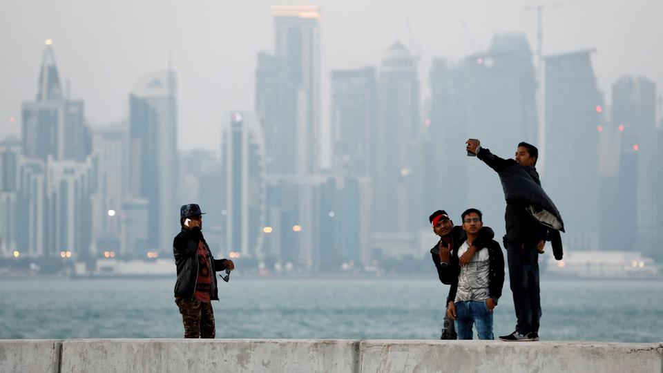 FILE PHOTO: Men take selfies near the sea in front of the skyline of Doha
