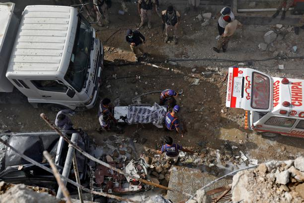 Rescue workers carry a victim at the site of a passenger plane crash in a residential area near an airport in Karachi