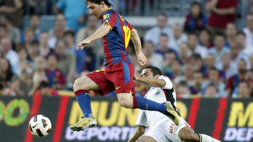 \'Barcelona\'s Lionel Messi goes past Real Mallorca\'s Joao Victor during their Spanish first division soccer match at Nou Camp stadium in Barcelona October 3, 2010.   REUTERS/Gustau Nacarino (SPAIN -