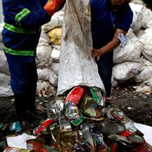 Workers from a recycling company dump garbage collected and brought from Mount Everest out of a bag, in Kathmandu