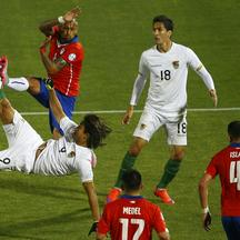 Bolivia's Marcelo Martins kicks the ball next to Chile's Arturo Vidal as Bolivia's Ricardo Pedriel and Chile's Gary Medel and Mauricio Isla look on during their first round Copa America 2015 soccer match at the National Stadium in Santiago, Chile, June 19
