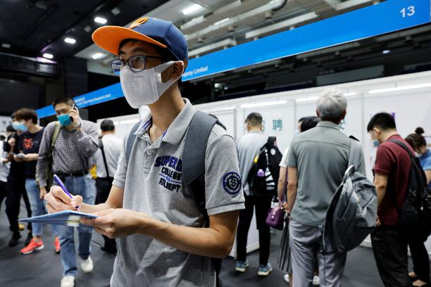 A job seeker wearing a face mask fills in forms at the Wan Chai Job Fair, following the coronavirus disease (COVID-19) outbreak, in Hong Kong