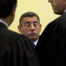'Former Croatian Army General Ante Gotovina (C) talks to his defence team in the court room before the International Criminal Tribunal for the former Yugoslavia (ICTY) as it delivers its judgment in t
