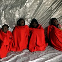 Migrants are covered with thermal blankets following a rescue operation of 104 sub-Saharan migrants aboard an overcrowded raft by the Spanish NGO Proactiva Open Arms, in the central Mediterranean Sea, 24 miles north of the Libyan coastal city of Sabratha,
